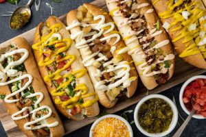 Five gourmet hot dogs on a table